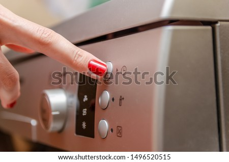 Female hand with red nail polish presses the button to adjust the time in the dishwasher #1496520515