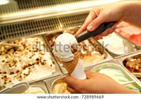 Female hand with scoop takes ice cream from the fridge and serving in waffle cone. Woman taking scoop of tasty ice cream. Fridge with ice cream. Woman works in ice cream shop. Pastry shop. Desserts.
