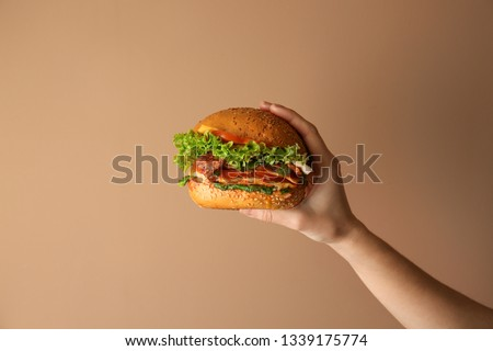 Female hand with tasty burger on color background