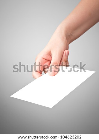 Female hand with the white virtual card on gray background