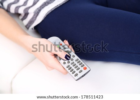 Female hand with TV remote control, close-up