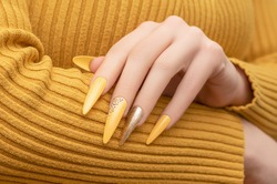 Female hand with yellow nail design. Long nail polish manicure. Woman manicure with gitter gold long nail art