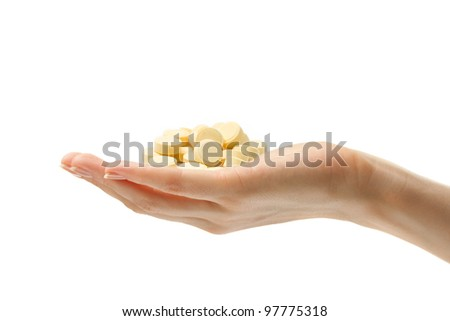 Female hand with yellow pills