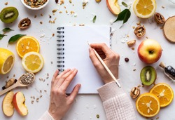 Female hand write in notebook on healthy food background, women diet nutrition recipe menu, fresh summer fruit granola seeds on white table organic super food, health care detox, top view, copy space