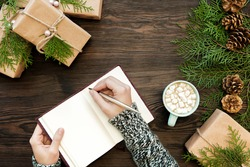 female hand writes Christmas letter in  notebook on dark boards with  gifts and fir cones
