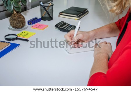 female hand writes in a notebook on a table background