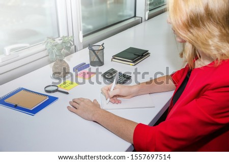 female hand writes in a notebook on the background of the table. Toned.