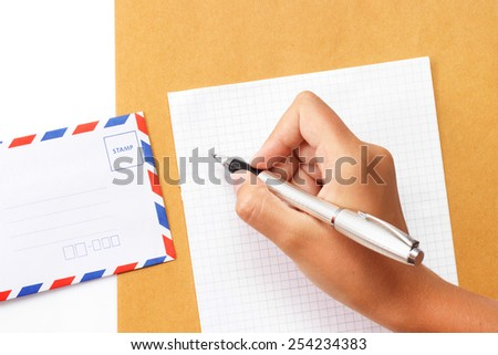 Female hand writing a letter on paper with envelope on the table view 1