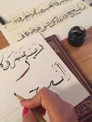 Female hand writing Arabic alphabet letters with wooden calligraphy pen and black ink.