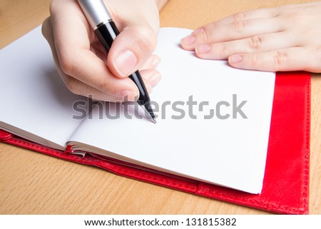 female hand writing in red notebook