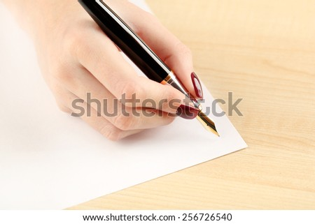 Female hand writing letter on white sheet of paper by fountain pen on wooden table background