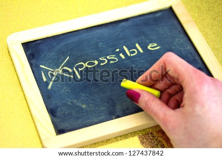 female hand writing on blackboard, impossible is possible