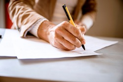 Female hand writing signature on the paper document. Cut out Woman signs agreement or formular contract. Paperwork concept