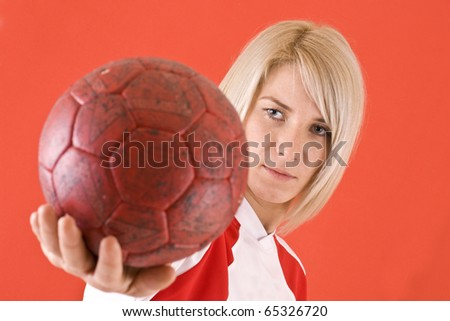 female handball player with a  ball,  in red background - stock photo
