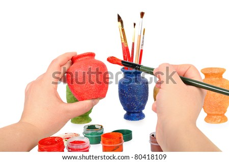 Female hands a brush paint a vase. Isolated on the white