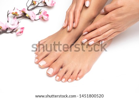 Female hands and feet with nice pedicure isolated on white background.