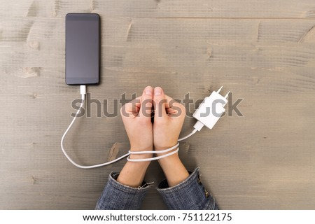 Female hands and smartphone. Woman's hands trapped and wrapped on wrists with mobile phone cable as handcuffs. Addiction to internet and social networks Stock foto ©