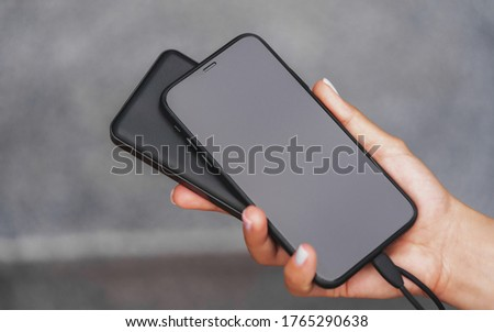 Female hands are holding a black phone and a black Powerbank charger. Still life modern digital concept. Foto stock ©