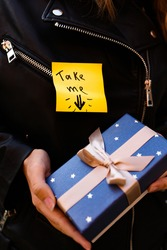 female hands are holding a blue gift box. A yellow sticker that says take me is pointing to a gift box. accept gifts concept