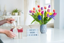 Female hands are opening gift box on marble table with colorful spring flowers bouquet in vase and lightbox with words Best mom ever. Light interior room. Happy Mother's Day background. Copy space