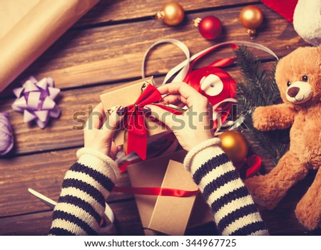 Female hands are wrapping a christmas gift on wooden background