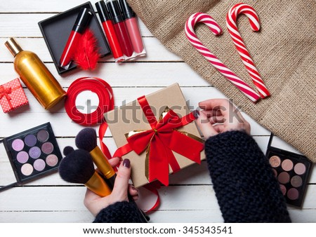 Female hands are wrapping cosmetics in christmas gifts on white wooden background
