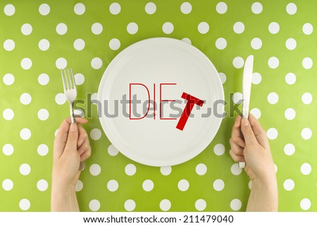Female hands at dinner table holding fork and a knife above plate as dieting concept Word Diet becoming Die referring to health issues that diet mistakes can cause
