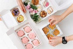 Female hands beautifully and carefully arranging colorful sweets in white windowed boxes. Zefir, cookies, macarons and cakes decorated with branches and flowers. Top view.