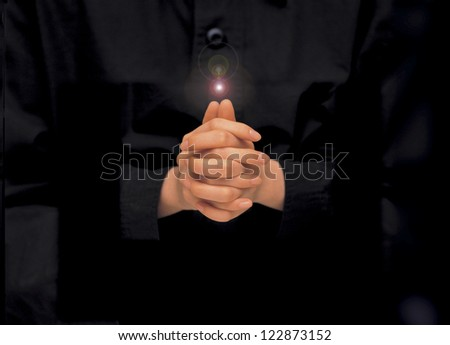 Female hands clasped for praying on black background - stock photo
