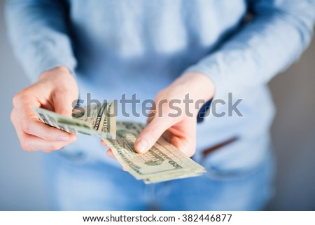 Female hands counting US Dollar bills or paying in cash. Shallow DOF.