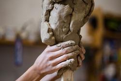 Female hands create a clay head sculpture in art studio