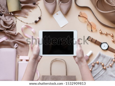 Female hands customer hold digital tablet computer mock up blank empty screen on beige fashion women stylish accessories background, online shopping app technology, black friday concept, top view