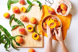 Female hands cutting fresh sweet peaches. Peaches whole fruits leaves, half peach, peach slices on white wooden kitchen table. Recipe making peach jam, cooking peach dessert on cutting board. Flat lay