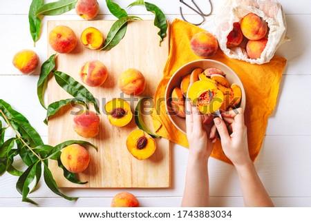 Female hands cutting fresh sweet peaches. Peaches whole fruits leaves, half peach, peach slices on white wooden kitchen table. Recipe making peach jam, cooking peach dessert on cutting board. Flat lay
