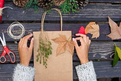 Female hands decorating a Christmas Gift with natural elements