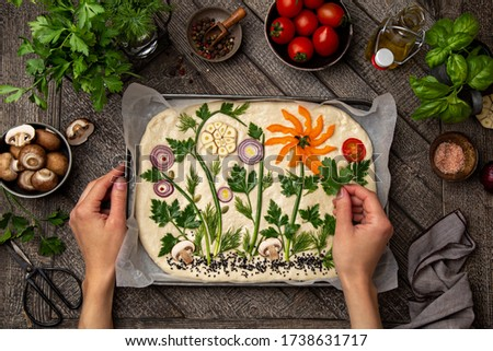 female hands decorating raw floral painting focaccia,  garden flatbread art, food trend. Old wooden background, top view