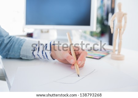 Female hands drawing with pencil on paper on her desk