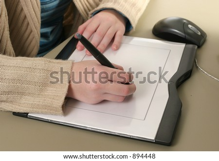 Female hands drawing with the stylus of a computer graphics tablet.