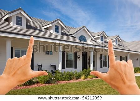 Female Hands Framing Beautiful House Over Blue Sky.
