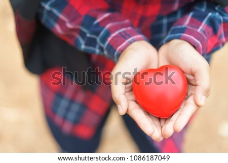 Female hands giving red heart,health, medicine and charity concept.