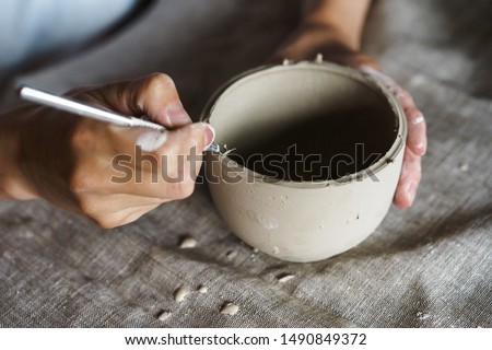 Female hands handle the edge of a wet clay bowl with a stick. Female hands hold a bowl for casting clay products. Shaped method for making clay dishes. Pottery making