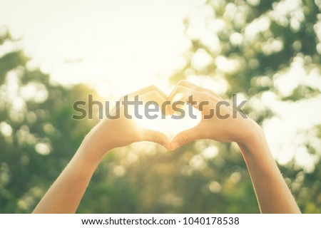 Female hands heart shape on nature bokeh sun light flare and blur leaf abstract background. Copy space of happy love and freedom concept. Vintage tone filter color style.