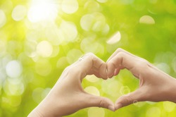 Female hands heart shape on nature green bokeh sun light flare and blur leaf abstract background. Copy space of happy love and freedom concept. Vintage tone color style.