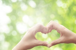 Female hands heart shape on nature green bokeh sun light flare and blur leaf abstract background. Copy space of happy love and freedom concept. Vintage tone filter color style.