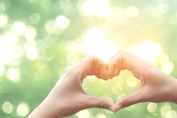Female hands heart shape on nature green bokeh sun light flare and blur leaf abstract background.