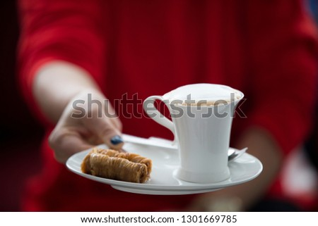 Female hands hold a aromatic beverage, drinks cappuccino or coffee cup on a saucer with a turkish dessert. Against the background of red sweater. blue manicure and nails.
