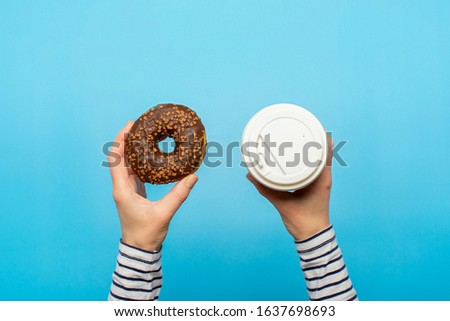 Female hands hold a donut and a paper cup with coffee on a blue background. Concept confectionery store, pastries, coffee shop. Banner. Flat lay, top view
