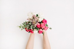 Female hands hold bridal flowers bouquet with roses, eucalyptus branch, wildflowers. Flat lay, top view wedding background.