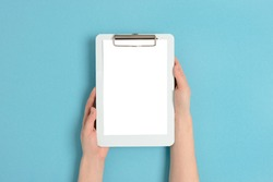 Female hands hold clipboard. Empty mockup on a blue pastel background.