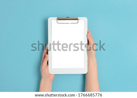 Female hands hold clipboard. Empty mockup on a blue pastel background. Foto stock ©